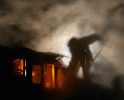 Fireman trimming coal at night in steam locomotive tender in China, photo by Scott Lothes